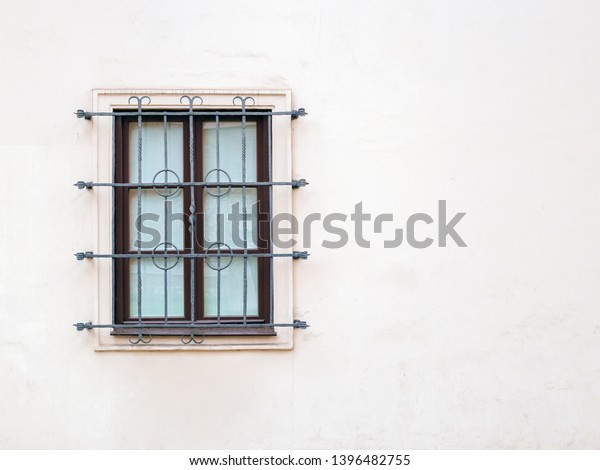Window with iron bar grill in stone wall for copy or text
