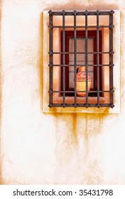 Window with iron bars and ceramics vase on a white wall