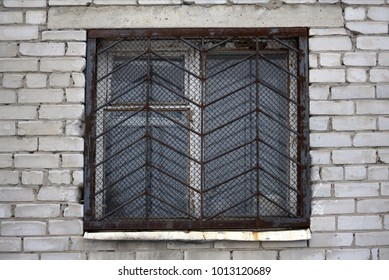 window with iron grating on stone wall