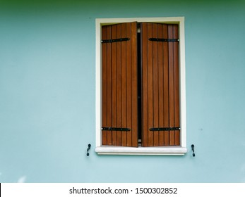 Window of an italian house on a blue wall
