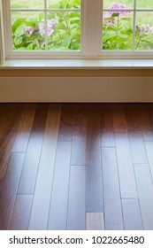 Window light reflecting shining on clean, polished wood hardwood floor in upscale home