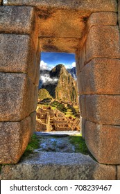 A window to Machu Picchu. Artistic HDR image of the magnificent view of the lost Incan city of Machu Picchu near Cusco, Peru through an ancient window