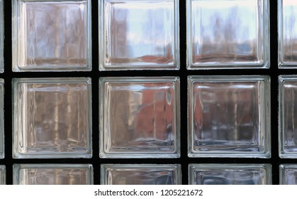 Window made of glass squares and black metal between them. You can see some colorful buildings through the glass pieces. A beautiful texture that can be used as a background or wallpaper for example.