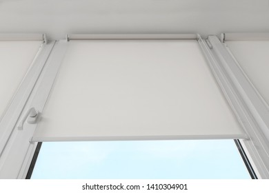 Window with modern roll blinds in room, closeup