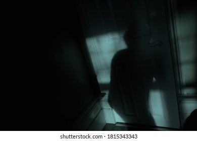 Window moonlight highlights the shadow of a mysterious creeping figure