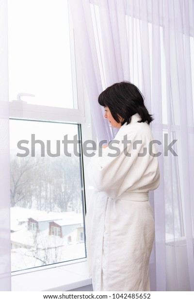 window morning light middle aged brunette woman in white coat