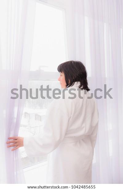 window morning light middle aged brunette woman in white coat