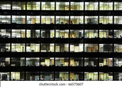 window of the multi-storey building of glass and steel office lighting and working people within
