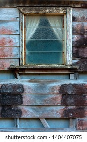 window in old weatherboard building with missing boards and framing