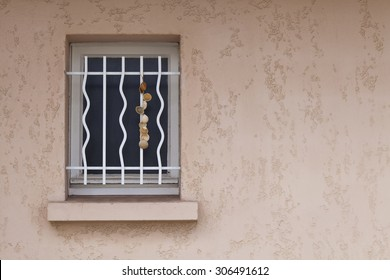 Window on a Beach Side cottage. A quirky grill and a hanging set of shells decorate a window on a seaside cottage in France.