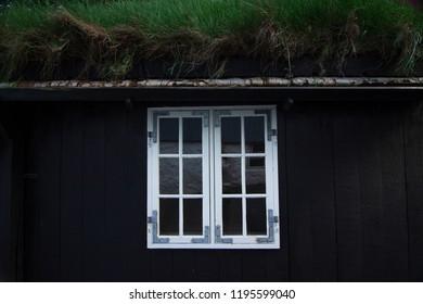 Window on black wall with grass roof in Torshavn, Faroe Islands, Denmark