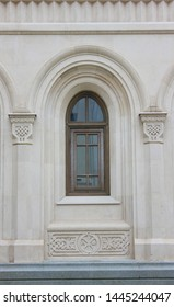 Window on church facade close up view of classic architectural detail. Single plain arched window on beige facade wall