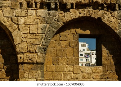 A window on a mediewal wall that shows the present life