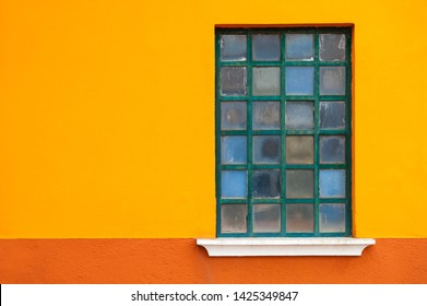 Window on the orange wall of the house. Colorful architecture in Burano island, Venice, Italy.