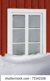 window on red cottage with snow and ice