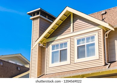 Window on upper level of residential building on blue sky background