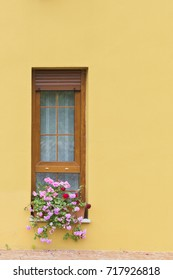 Window on a yellow wall. A window with a brown wooden frame and bright colors on a window sill on a wall with yellow plaster. Outdoor