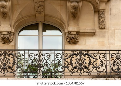 Window of one of the beautiful buildings along Champs Elysees avenue with typical wrought iron fences and modeling, Paris, France