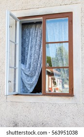 A window open to let some fresh air in through the lace curtains on a summer day.