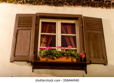 A window with open shutters beds with red curtains