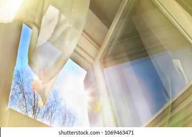 Window is open, wind blows, curtain moves, sun is shining in the window.