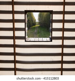 The window in the outdoors. Wall with square window without glass that goes into the woods