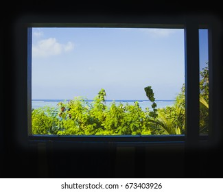 Window overlooking view the blue ocean, sky and coral reef. Window on dream vacation.