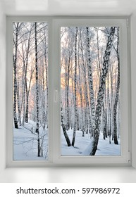 Window overlooking the winter morning landscape with sunrise and birch trees hoarfrost covered. Beautiful view from window