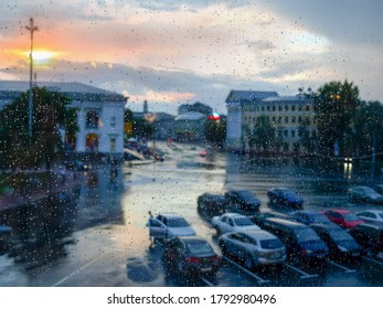 Window pane during a rain, blurred cityscape through the wet glass covered with water drops at sunset, inside view, background