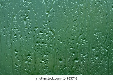 Window pane on a rainy day, green blurry background