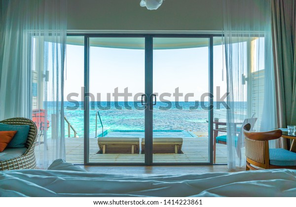 window with pool and sea background at Maldives - view from bed