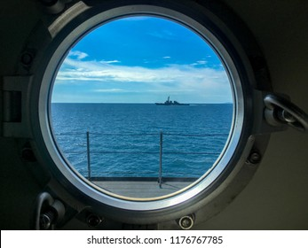 Window port of navy ship with dogs for locking the window. Outside the window also has destroyer sails beside the observer's ship.