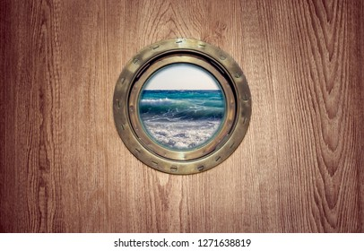 Window porthole on board the ship overlooking the sea with waves - view of the storming ocean during a storm. Brass porthole frame on an old sailboat for your nautical poster with place for text.
