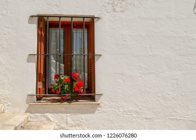 The window of a quintessentially Spanish house with red flowers in a window box, Mahon, Menorca, Balearic Islands