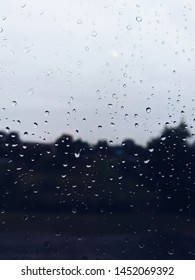 window with raindrops overlooking the road