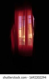 Window with red curtain in a dark room