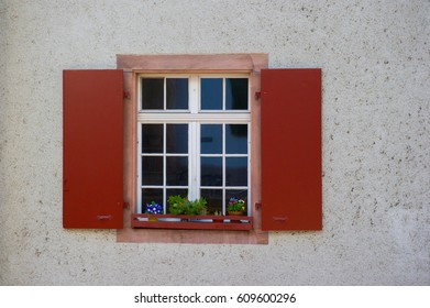 window with red wooden shutters and flower pots
