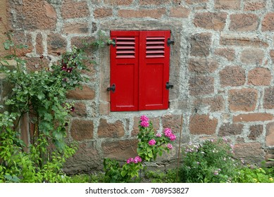 Window with red wooden shutters in an old stone facade with flower garden in the foreground