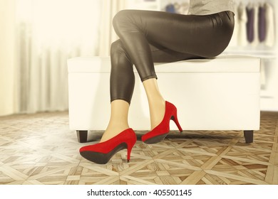 window in room and brown floor and red heels and legs