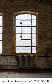 Window of a ruined factory with mat old glass and iron in a brick wall in a lost place in Germany