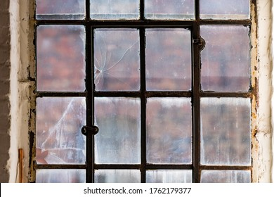 Window of a ruined factory with old mat glass and iron in a brick wall in a lost place in Germany