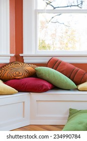 Window seat with colorful pillows. Close up bright sunny image. Vertical