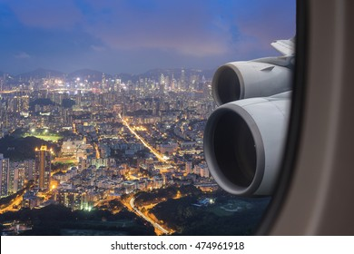 Window seat on airplane overlooking Hong Kong night view . Jet engine on the wing , on fly .