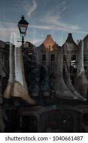 The window of a shoe repair shop with reflection of authentic dutch homes in Oudewater, The Netherlands.