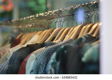 window shopping with hanging shirt,jacket,on a wood hanger through  glass window with bokeh reflection