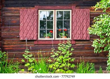 Window with window shutters on an old Swedish log cabin.