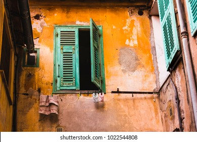 Window with shutters on orange wall and laundry on the line in Villefranche-sur-mer alley, France