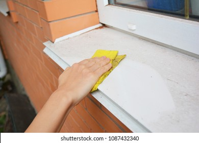 Window sill cleaning from dust. Woman cleaning  windows and window sills.