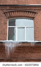 Window sill covered with big icicles, vertical. ice stalactite hanging from window sill. Poor thermal insulation of the roof leads to the formation of icicles. Many little icicles