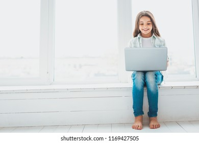 Window sill. Long-haired beautiful schoolgirl feeling busy while sitting on window sill at home